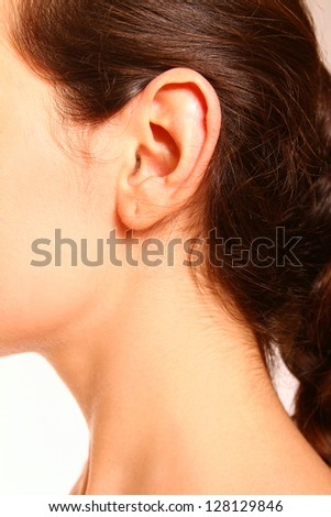 A close-up portrait of a female ear and neck on white background - stock photo