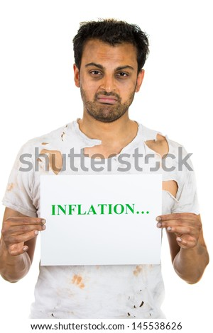 A close-up portrait of a homeless broke former executive man holding a sign which says inflation, isolated on a white background  - stock photo