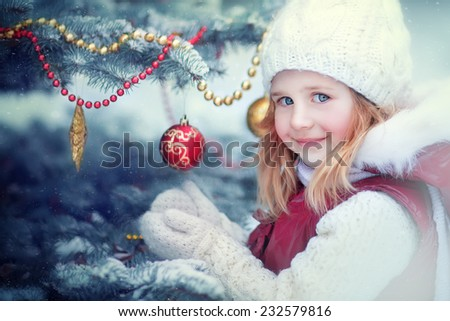 A close up portrait of a little cute smiling girl in a white knitted cap and mittens standing near the decorated Christmas tree on a frosty winter day outdoor.  - stock photo