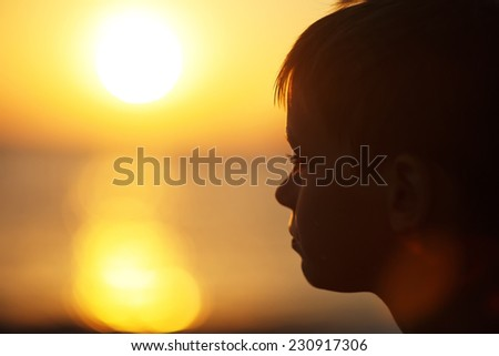 A close up portrait of a little happy boy walking on the sea shore on a warm summer evening  - stock photo