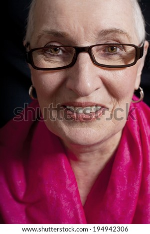 A close up portrait of a senior woman with a pink shawl over her shoulders. - stock photo