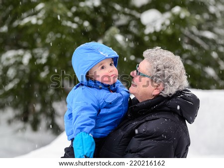 A close up portrait of a smiling grandmother looking at her happy grandson while holding him outside while its snowing during the winter season  - stock photo