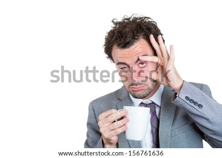 A close-up portrait of a very tired, falling asleep businessman holding a cup of coffee, struggling not to crash and stay awake, keeping his eyes opened, isolated on a white background with copy space - stock photo