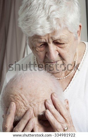 A Close-up portrait of an elder couple at home. The couple having proble. the men have the hand on the face and the woman look to the floor. - stock photo