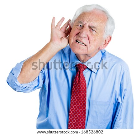 A close-up portrait of an elderly executive looking unhappy and annoyed,having trouble hearing his opponent, during unpleasant conversation, isolated on a white background . Hearing aid. - stock photo