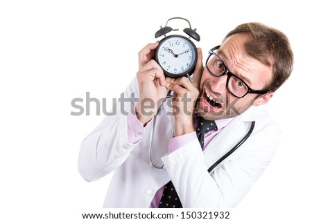 A close-up portrait of an overwhelmed busy unhappy male doctor holding an alarm running out of time isolated on a white background . - stock photo