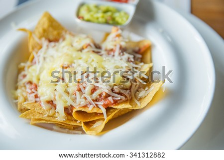 A close up portrait of mexican food nachos with sauce and cheese