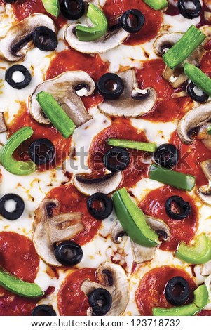 A close-up portrait of pizza with toppings of mushroom, salami, bell pepper and black olives - stock photo