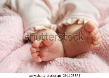 A close up portrait of the bottoms of a newborn baby girl's feet on pink blankets.