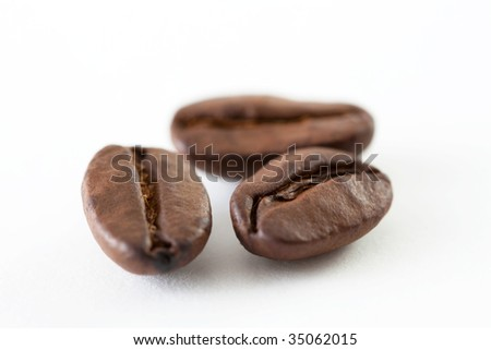 A close up shoot of some coffee beans isolated on white background
