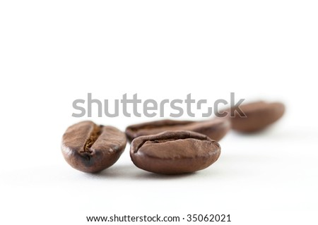 A close up shoot of some coffee beans isolated on white background - stock photo
