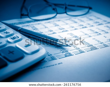 A close-up shot of a calculator.  A printed balance sheet and a pen are also visible. - stock photo