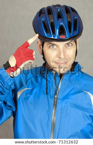 A close-up shot of a cyclist pointing at his helmet. - stock photo