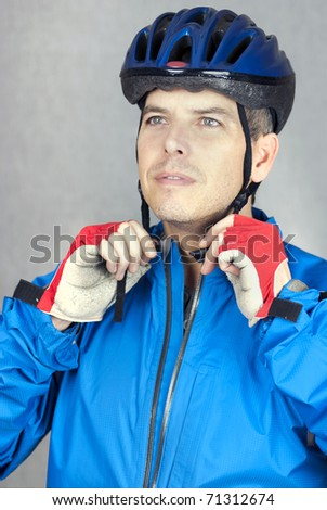 A close-up shot of a cyclist putting on his helmet. - stock photo