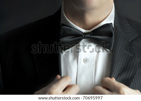 A close-up shot of a man straightening his tux. - stock photo