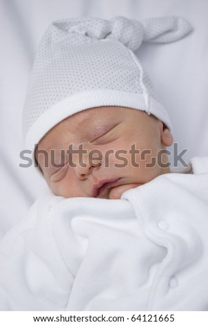 A close up shot of a new born baby less than one week old. He lays asleep on a white backdrop in white clothing. studio set up of one key light and a bounced flash with a shallow depth of field.