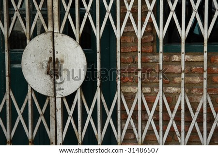 A Close up shot of a old rusty gate of a traditional shophouse. - stock photo