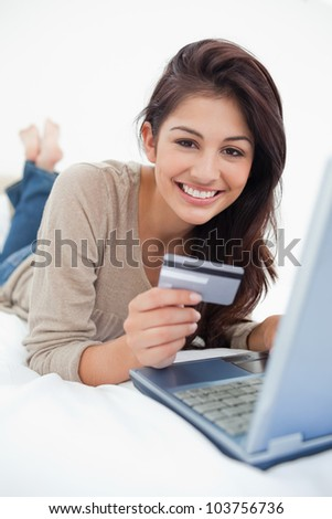 A close up shot of a smiling woman on the bed with a credit card in hand and a laptop in front of her. - stock photo