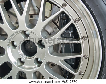 A close up shot of a sports car wheel and brakes - stock photo