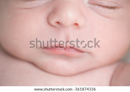 A close-up shot of a three week old, newborn baby boy's lips. - stock photo