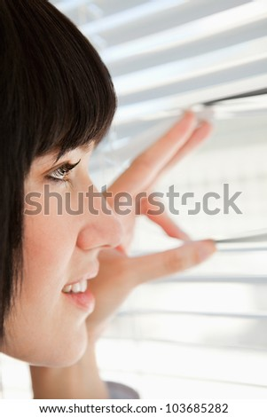 A close up shot of a woman looking through her window blinds - stock photo