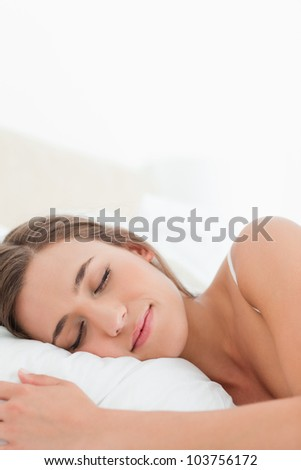 A close up shot of a woman sleeping with her head on the pillow.