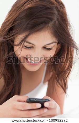 A close up shot of a woman smiling as she interacts with her smartphone. - stock photo