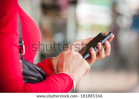 A close-up shot of a woman texting, or using a smartphone cell phone. - stock photo