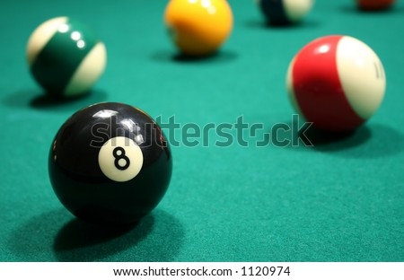 A close-up shot of an eight ball on a green felt covered pool table with several other billiard balls nicely blurred in the background.