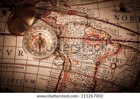 A close-up shot of an open brass compass on a antique, 1920's map. - stock photo