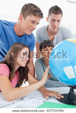 A close up shot of four people sitting in front of the globe and looking for a place - stock photo