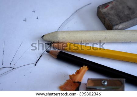 A close up shot of two pencils, a tortillon, a pencil sharpener, pencil shavings, and a blackened eraser pictured on white paper, with a simple sunrise sketch. - stock photo