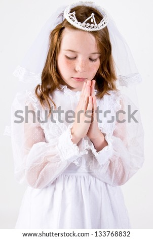 A close-up, shot straight on, of a young girl praying in her First Communion Dress and Veil - stock photo
