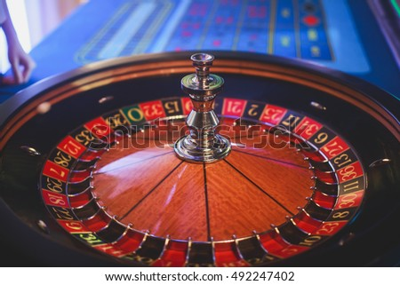 A close-up vibrant image of multicolored casino table with roulette in motion, with the hand of croupier, and a group of gambling rich wealthy people in the background