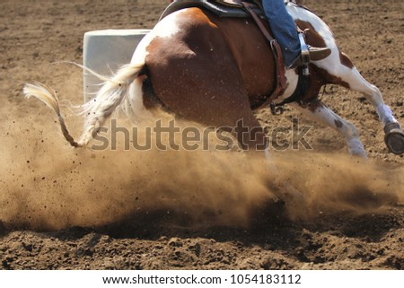 A close up view of a barrel racing horse kicking up dirt and dust sliding around the barrel.