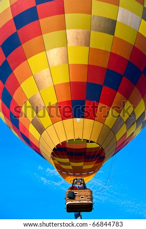 A close-up view of a colorful balloon flying in a blue sky. - stock photo