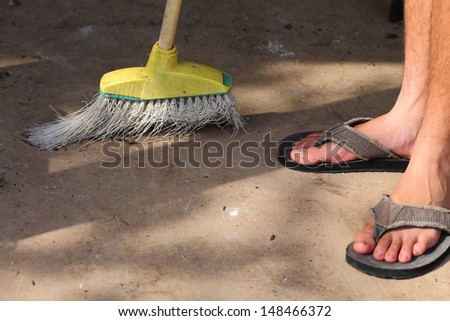 A Close up view of a yellow plastic broom with white bristles - stock photo