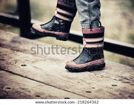 A close up view of a young boys feet wearing fireman rain boots.  The boots are dirty with mud.  Filtered to give retro, vintage look.  - stock photo