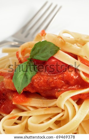 A Close Up View Of Fresh Fettuccine With Spaghetti Sauce And Basil Leaf