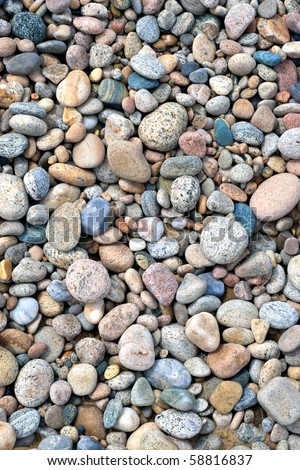 A close up view of smooth polished multicolored stones washed ashore on the beach. - stock photo