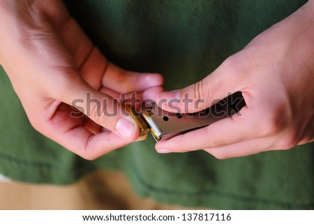 A close up view of someone loading 380 caliber bullets into a ammo clip for a gun - stock photo