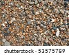 A close up view of wet pebbles and stones washed ashore on the beach. - stock photo