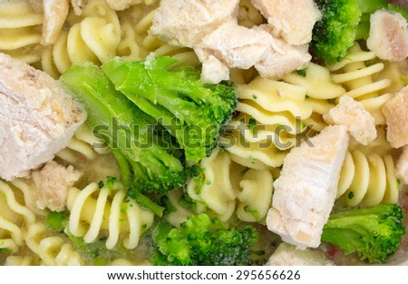 A close view of grilled chicken with spiral noodles and broccoli. - stock photo