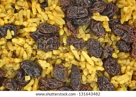 A close view of spicy rice and raisins. - stock photo