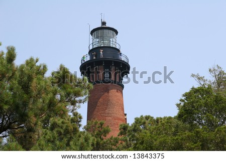 A close view of the top of Currituck Beach Lighthouse with tree tops.