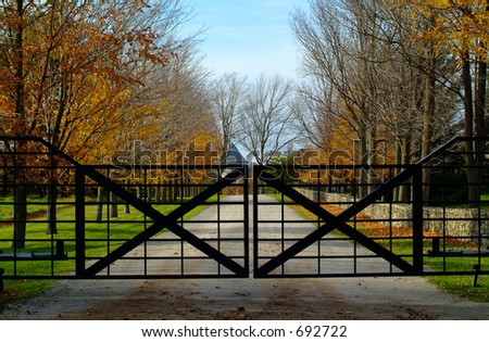 A closed gate hides a long driveway to a country estate
