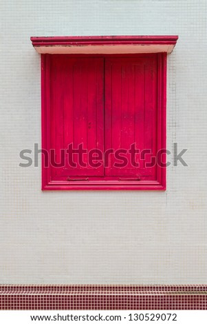 A closed red window on the wall - stock photo