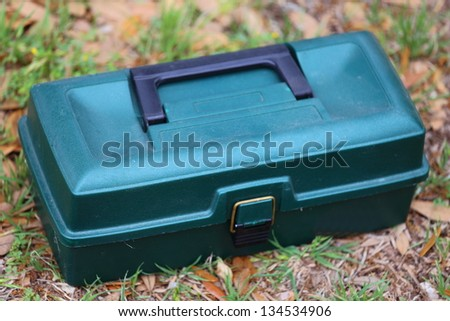 A closed tackle box sitting on the grass waiting to be used - stock photo