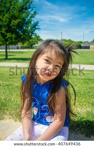 A closed up of little girl  playing sand at public park  with blue sky background,filtered color tone in picture. - stock photo