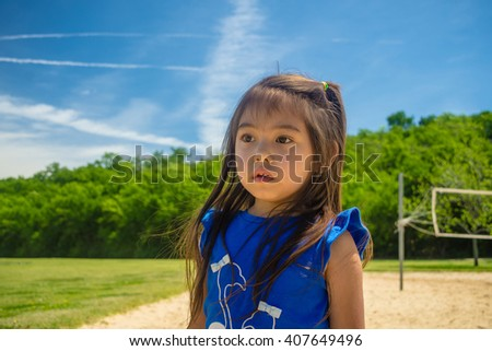 A closed up of little girl walking on sand at public park  with blue sky background,filtered color tone in picture.